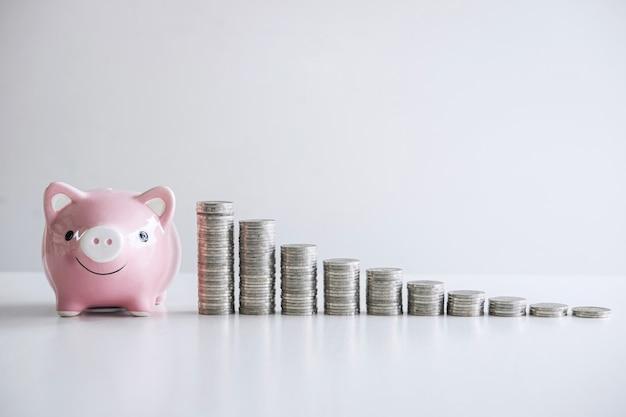 Immagini di impilare il mucchio di monete e salvadanaio sorridente rosa per crescere e risparmiare con salvadanaio, risparmiando denaro per il piano futuro e il concetto di fondo pensione