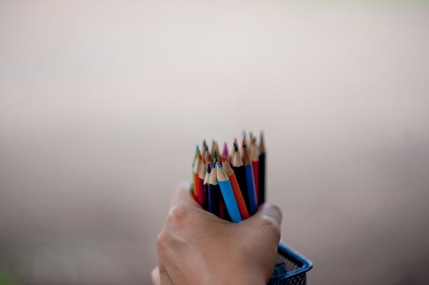 Immagini di mano e matita, colore di sfondo verde concetto di educazione