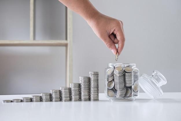 Immagini di monete impilabili in crescita e mano che mette la moneta in una bottiglia di vetro (salvadanaio) per pianificare passi avanti e risparmi, risparmiare denaro per il piano futuro e il concetto di fondo pensione