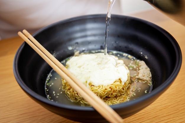 Immergendo acqua bollente nella fine della tagliatella istantanea del formaggio in su.