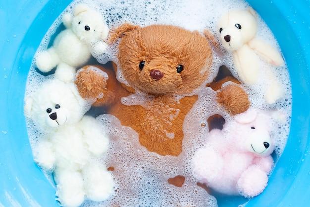 Immergere gli orsi giocattolo nella dissoluzione dell'acqua detergente per bucato prima del lavaggio. concetto di lavanderia,