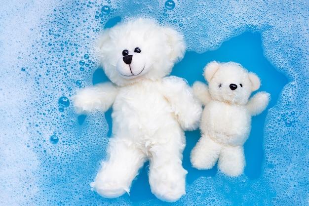 Immergere gli orsi giocattolo nella dissoluzione dell'acqua detergente per bucato prima era