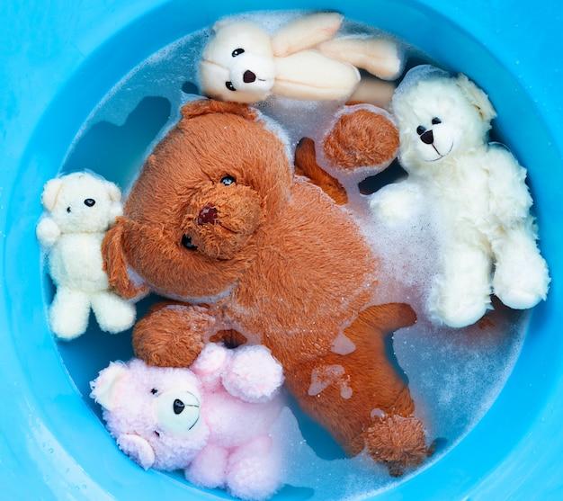 Immergere gli orsi giocattolo nella dissoluzione dell'acqua detergente per bucato