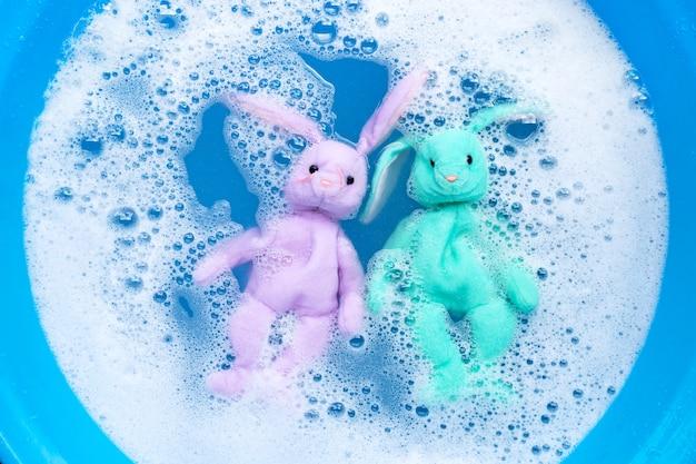Immergere i giocattoli delle bambole di coniglio nella dissoluzione dell'acqua del detersivo per bucato prima del lavaggio. concetto di lavanderia,