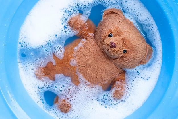 Immergere l'orso giocattolo nella dissoluzione dell'acqua detergente per bucato prima del lavaggio. concetto di lavanderia,