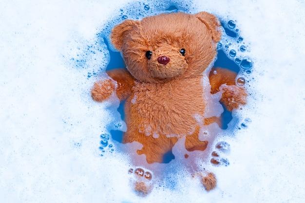 Immergere l'orso giocattolo nella dissoluzione dell'acqua detergente per bucato prima era