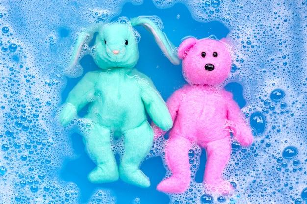 Immergere la bambola di coniglio con l'orsacchiotto giocattolo nella dissoluzione dell'acqua del detersivo per bucato prima del lavaggio. concetto di lavanderia,