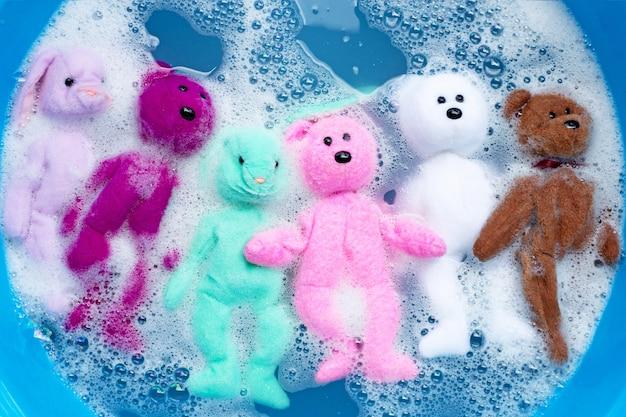 Immergere la bambola di coniglio con l'orsacchiotto giocattolo nella dissoluzione dell'acqua del detersivo per bucato prima del lavaggio. concetto di lavanderia