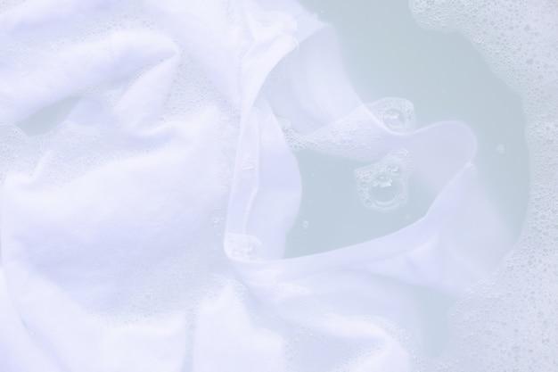 Immergi il panno prima di lavarlo, la maglietta bianca