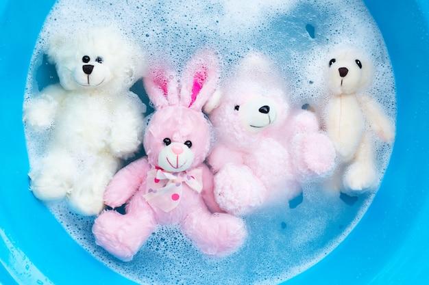 Immergi la bambola di coniglio con gli orsetti nel diss di acqua detergente per bucato