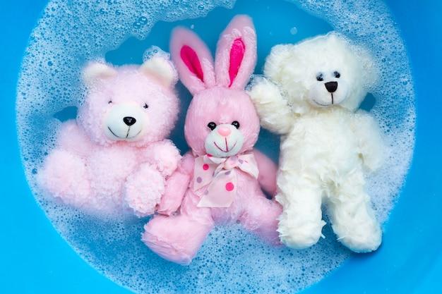 Immergi la bambola di coniglio con gli orsi giocattolo in acqua detergente per bucato