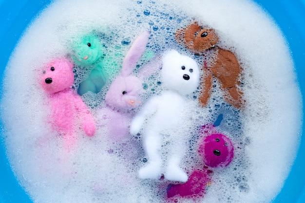 Immergi le bambole di coniglio con i giocattoli dell'orso nella dissoluzione dell'acqua del detersivo per bucato prima del lavaggio. concetto di lavanderia,