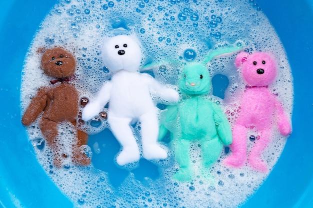 Immergi le bambole di coniglio con i giocattoli dell'orso nella dissoluzione dell'acqua del detersivo per bucato prima del lavaggio. concetto di lavanderia