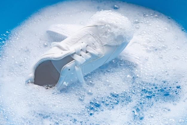 Immergi le scarpe prima di lavarle. pulizia di scarpe da ginnastica sporche.
