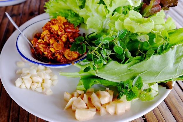 Immersione affumicata tailandese del peperoncino rosso del gamberetto con le verdure e l'aglio sul piatto bianco