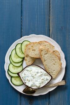 Immersione del cetriolo con pane sul piatto