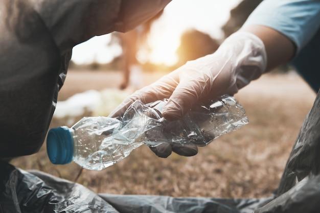 Immondizia della bottiglia della tenuta della mano che mette dentro alla borsa nera per riciclare pulizia