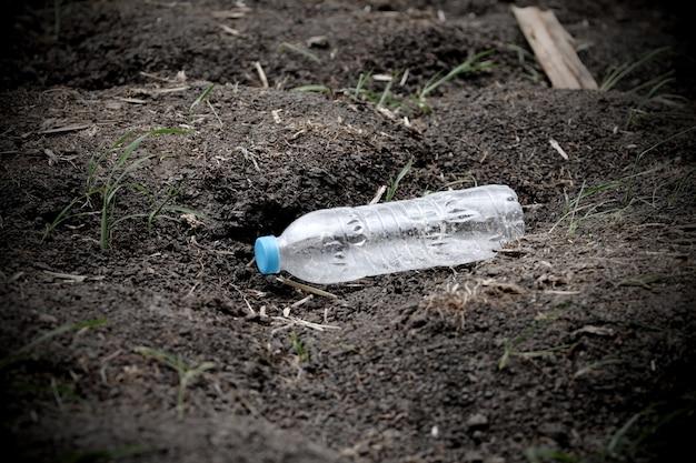 Immondizia della bottiglia di plastica sulla terra del suolo che può riciclare