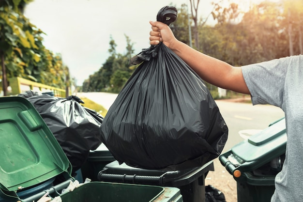 Immondizia della tenuta della mano della donna in borsa nera per la pulizia dentro per spazzare