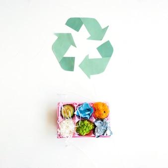 Immondizia nel cartone vicino al logo di riciclo