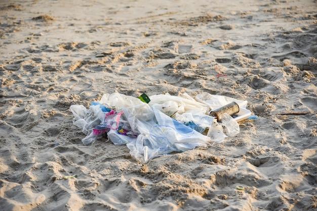 Immondizia nel mare con la bottiglia di plastica della borsa e l'altra spiaggia sabbiosa dell'immondizia