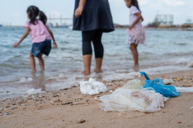 Immondizia sulla spiaggia con la famiglia che gioca acqua nel mare su fondo