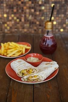 Impacchi di shawarma serviti con salsa e patatine fritte