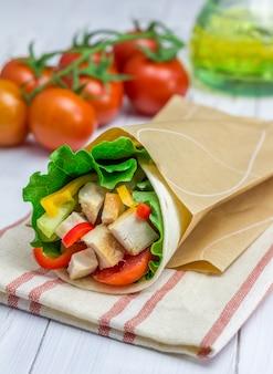 Impacchi di tortilla con filetto di pollo arrosto, verdure fresche e salsa