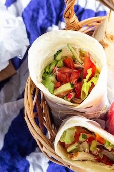 Impacchi di tortilla con pollo arrosto e verdure, succhi di frutta, verdure e frutti di bosco, baguette e formaggio.