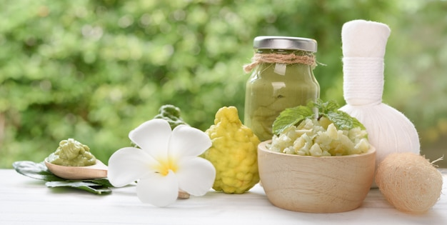 Impacco di massaggio alle erbe in stile tailandese con bergamotto fresco e citronella in vassoio di legno decorato da fiori freschi di frangipani o plumeria e pigna secca, per il concetto di assistenza sanitaria e spa