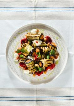 Impacco di melanzane alla griglia con hummus di peperone rosso e yogurt piccante sul tavolo. deliziosa ricetta vegana