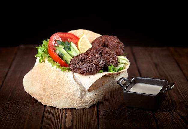 Impacco di tortilla con falafel e insalata fresca. tacos vegani. cibo vegetariano sano.
