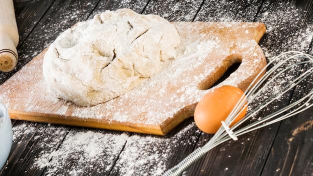 Impastare la pasta e l'uovo con il baffo sul tavolo della cucina