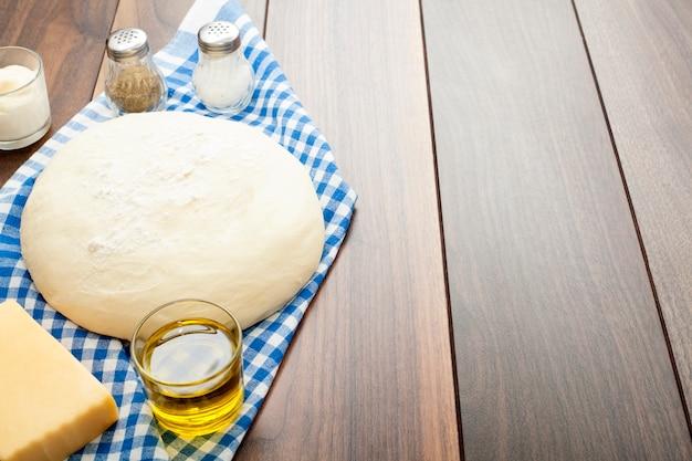 Impasto su un tavolo di legno, su un tovagliolo da cucina blu, con olio d'oliva, sale e pepe e panna acida