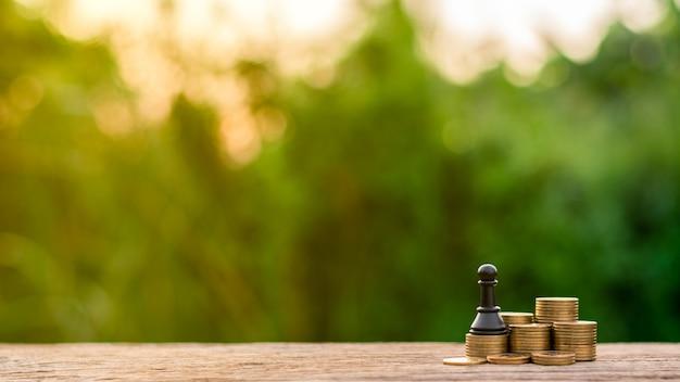 Impegni gli scacchi sulle monete dorate della pila. - combattere e vincere il concetto di business.
