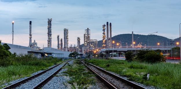 Impianto di produzione industriale di petrolio e gas con la ferrovia in primo piano alla sera