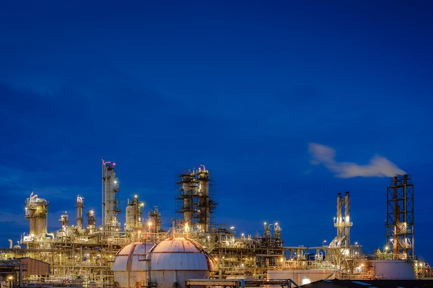 Impianto di raffineria di petrolio e gas o impianto industriale petrolchimico su sfondo di crepuscolo di cielo blu, fabbrica di illuminazione glitter di impianto petrolifero con cielo all'alba