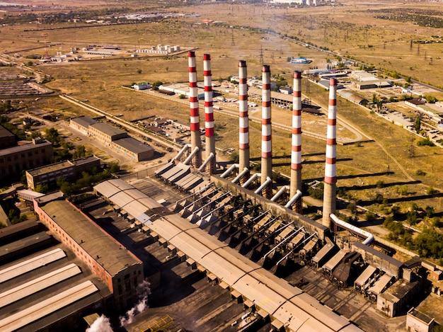 Impianto elettrico di potenza aerea con alti tubi industriali in una giornata estiva f