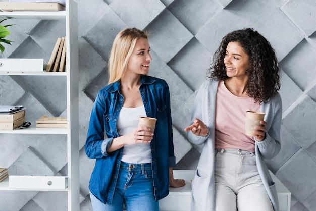 Impiegati di ufficio etnici femminili all'intervallo per il caffè