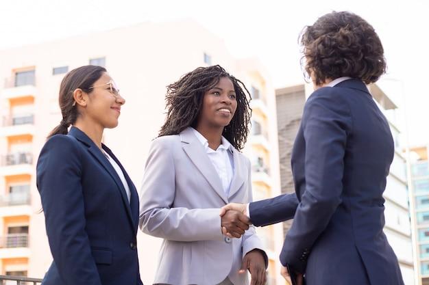 Impiegati sorridenti che stringono le mani sulla via. colpo potato di giovane riunione multietnica delle donne di affari all'aperto. attività commerciale