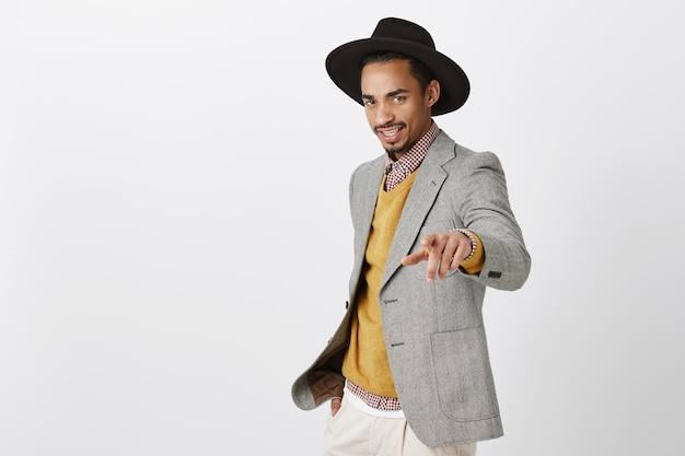 Impiegato alla moda che parla con i datori di lavoro, dando nuovi compiti. fiducioso modello maschile dalla pelle scura alla moda con cappello nero alla moda e giacca grigia che punta, essendo sicuro di sé sul muro grigio