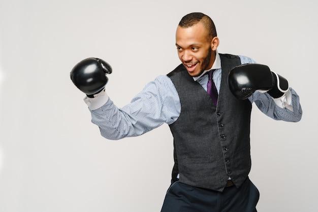 Impiegato arrabbiato giovane impiegato, impiegato di affari, pugni in aria con guantoni da boxe, bocca aperta che urla e grida, sensazione di emozione negativa espressione facciale.