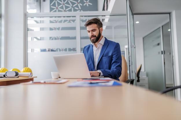 Impiegato barbuto caucasico concentrato giovani che si siede nel suo ufficio e che per mezzo del computer portatile per la stesura del rapporto.