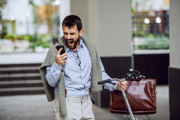 Impiegato caucasico alla moda barbuto nervoso che spinge la sua bici, tenendo smart phone e urlando. concetto di lavoro straordinario.