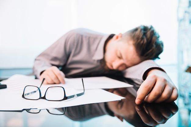 Impiegato che dorme in ufficio