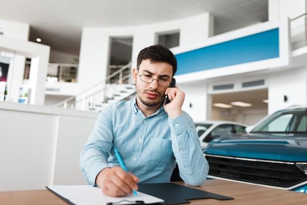 Impiegato del concessionario auto sul posto di lavoro sta parlando al telefono.