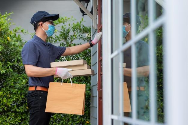 Impiegato del fattorino in maschera uniforme t-shirt cappuccio blu e guanti medici offre cibo da asporto. servizio di consegna in quarantena, epidemia di malattia, condizioni pandemiche di coronavirus covid-19.