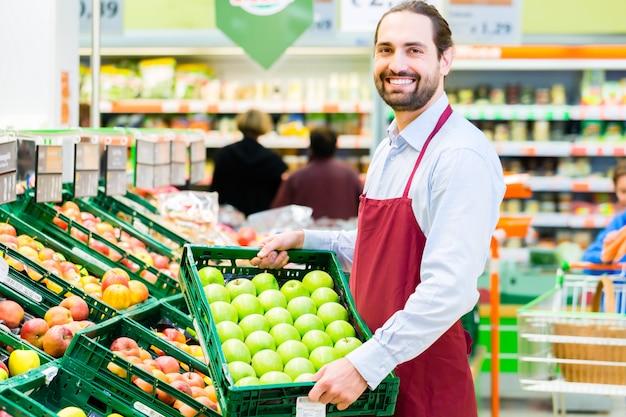 Impiegato dell'ipermercato che riempie gli scaffali di stoccaggio