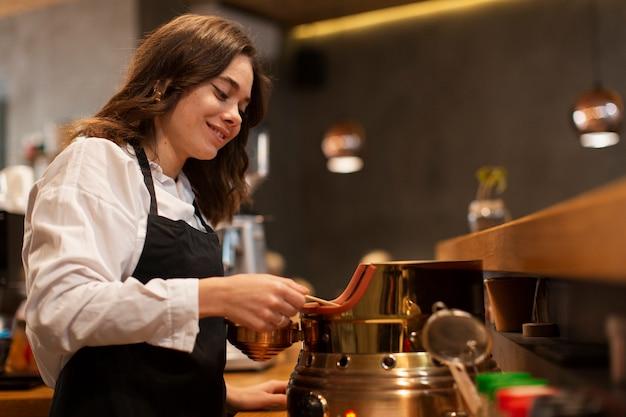 Impiegato della caffetteria che produce caffè