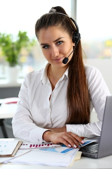 Impiegato di call center sorridente bella bruna al lavoro